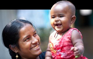 Äiti nostaa iloisena hymyilevää lasta.