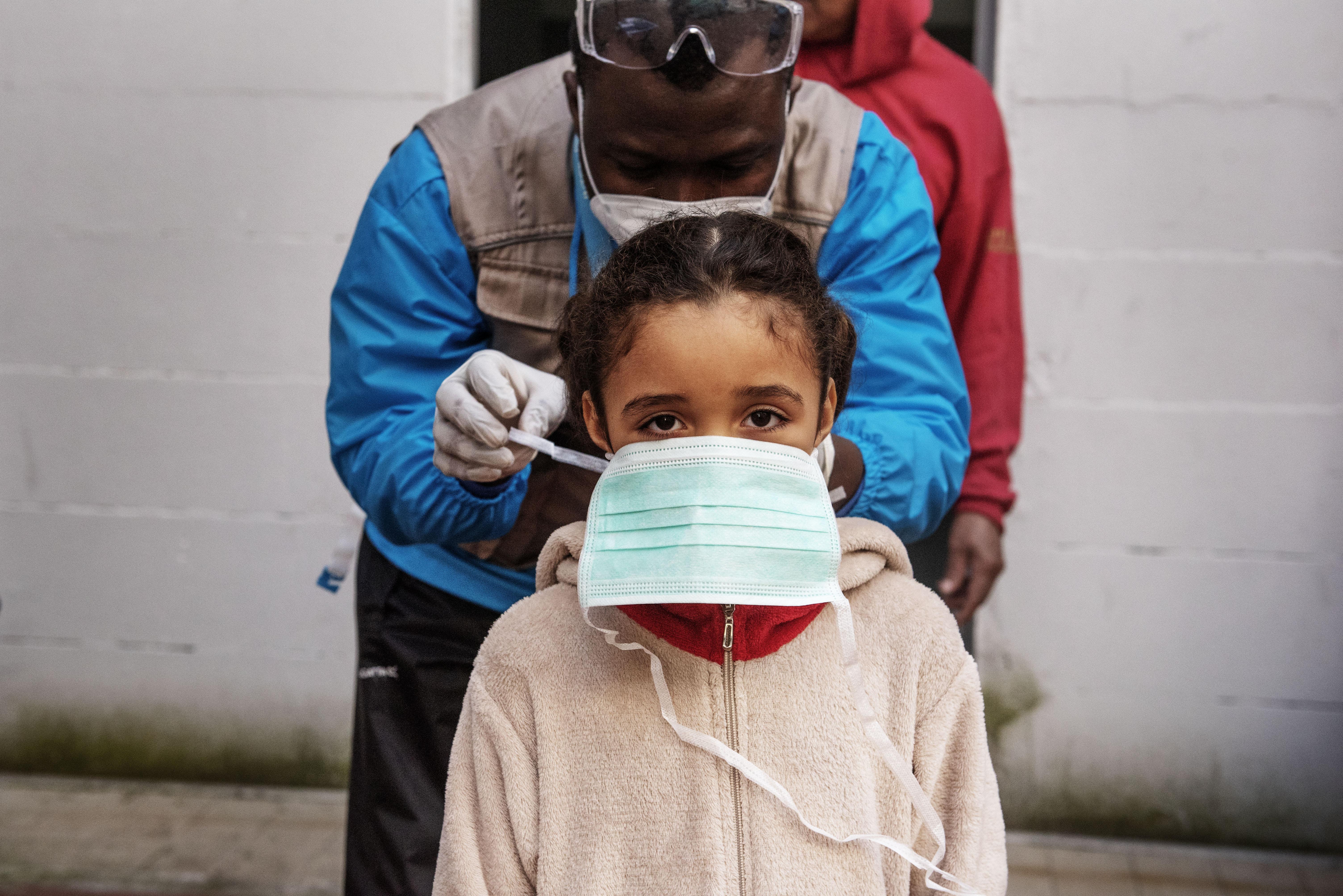 UNICEFin partnerijärjestön INTERSOSin työntekijä Abdoul Bassite ojentaa maskin terveystarkastukseen valmistautuvalle Francescalle, 7.