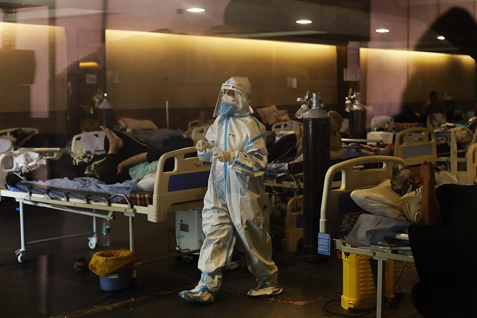 Suoja-asuinen terveystyntöntekijä kävelee sairaalassa potilaiden keskellä.