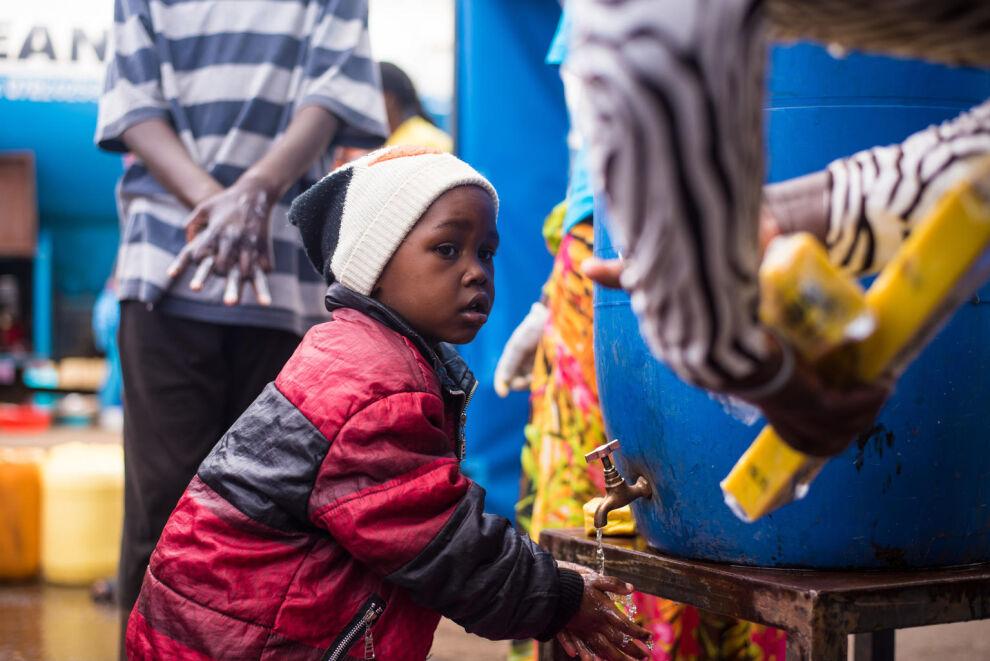 Pieni poika seuraa käsienpesuohjeistusta Kenian pääkaupungin Nairobin valtavalla Kiberan slummialueella. UNICEF tukee maata ehkäisemään koronaviruksen leviämistä. © UNICEF/UNI322682/Ilako