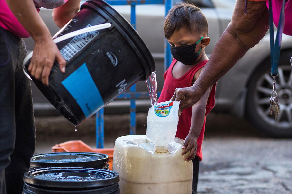 pieni lapsi on huoltajansa mukana vedenhakureissulla maan pääkaupungissa Caracasissa, Venezuelassa.