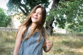 Hymyilevä nuori tyttö hammasraudoissa.