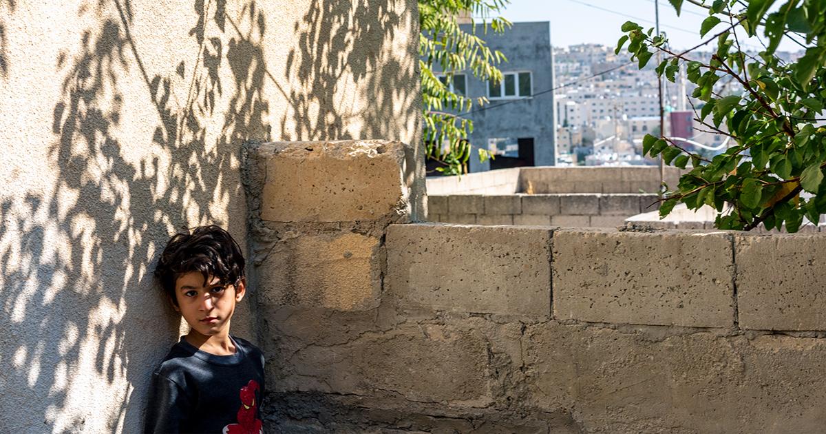 7-vuotias Ali nojaa uuden kotitalonsa seinään Jordaniassa. Ali joutui pakenemaan perheensä kanssa Syyrian sotaa.