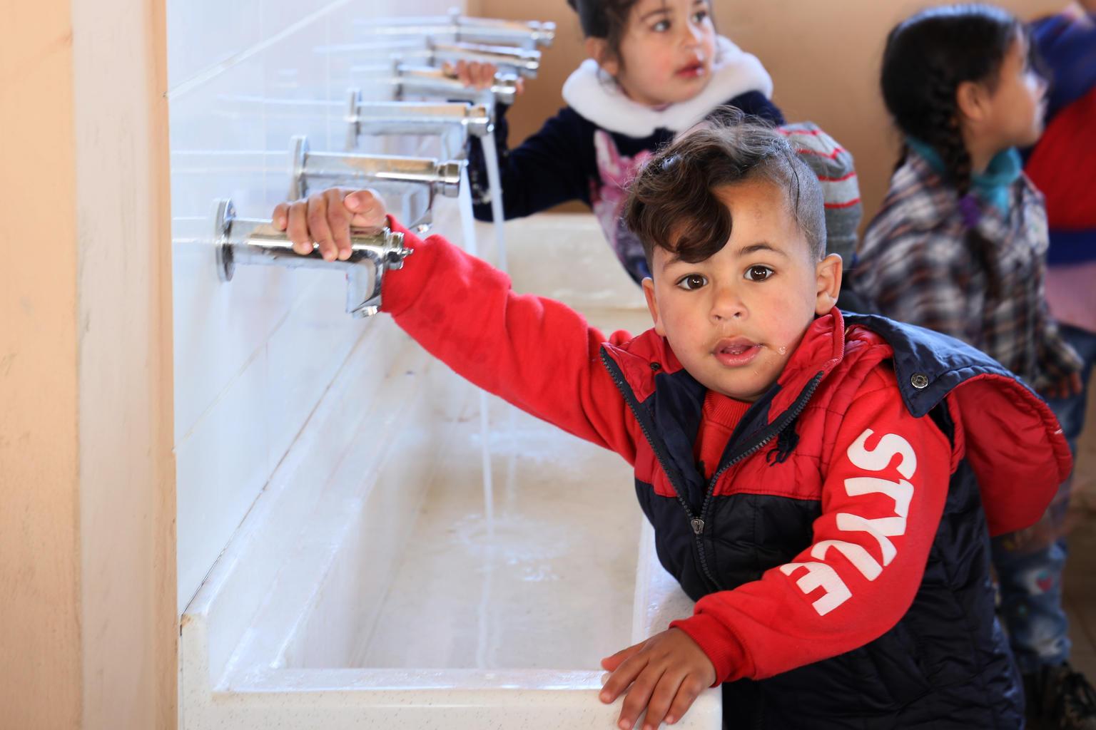 Oppilaat pesevät kätensä uudessa vesipisteessä. UNICEF kunnosti Hnayderin koulun tukeakseen syyrialaisten pakolaisten koulunkäyntiä Libanonissa. Kuva: © UNICEF/UNI315740