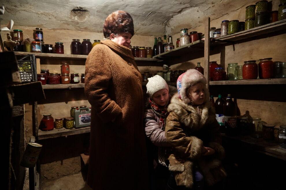 Itä-Ukrainassa sisarukset Diana (keskellä) ja Sasha piiloutuvat pommitusten aikana isoäitinsä Ninan kanssa talon kellariin. Kuva: © UNICEF/UN053113/Zmey