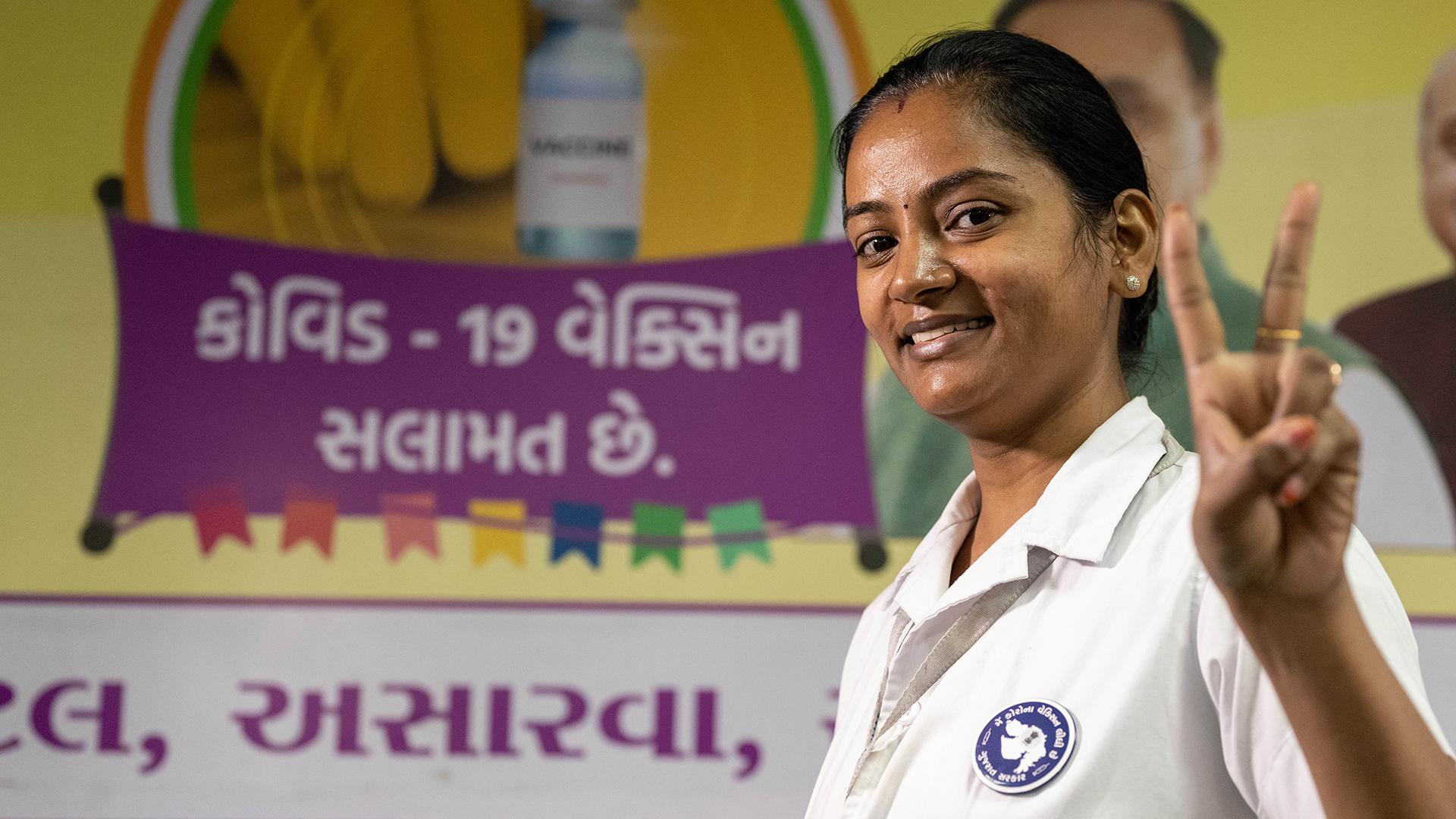 Sairaanhoitaja näyttää sormillaan V-voitonmerkkiä Intiassa