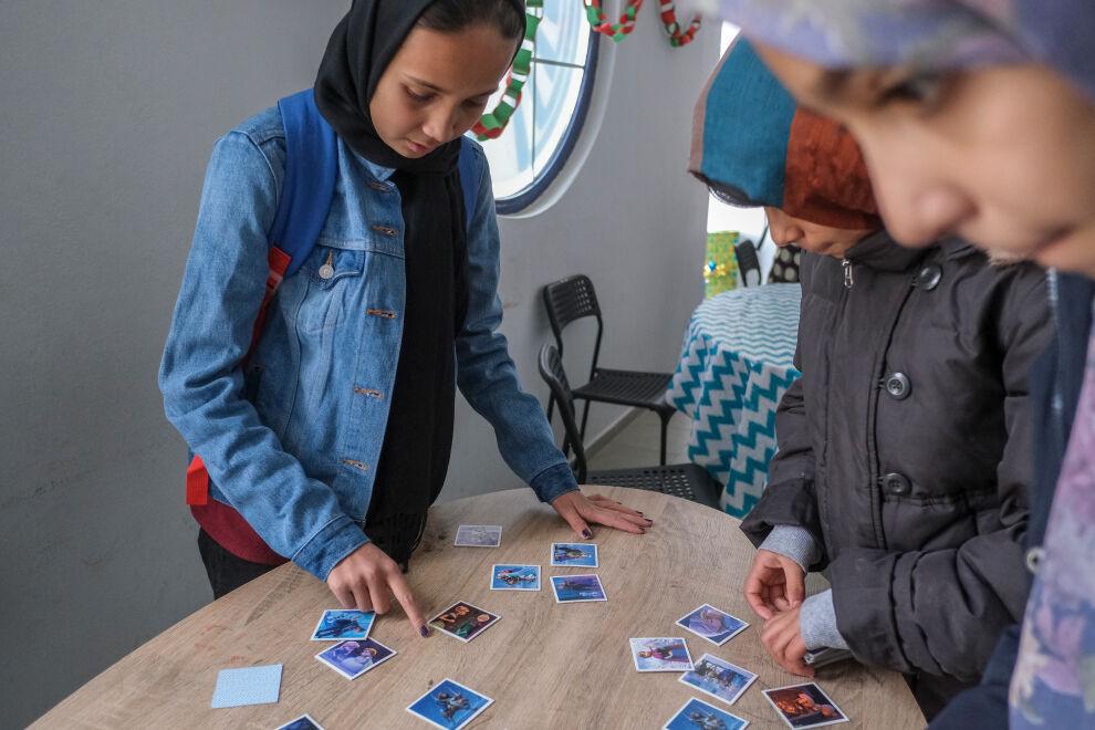 Lapset pelaavat Frozen-korteilla tilassa, jonka ovat järjestäneet UNICEF ja sen kumppanijärjestö Better Days. TAPUAT-niminen lapsi- ja perhekeskus sijaitsee Lesvoksen saarella Kreikassa. Lapset asuvat vastaaanotto- ja tunnistuskeskuksessa Moriassa. © UNICEF/UN0274821/Haviv VII Photo