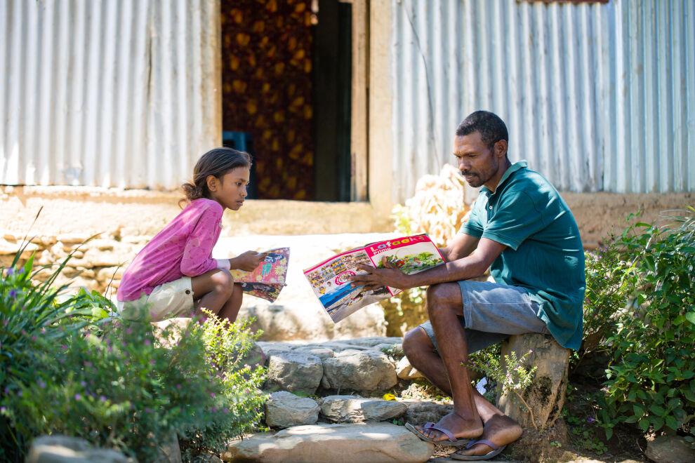 Cristina Elena Mendonca, 10 vuotta, saa apua koulutehtäviinsä isältään Joaquimilta Fahiriassa, Itä-Timorissa. Kuva: © UNICEF/UNI329961/Soares.