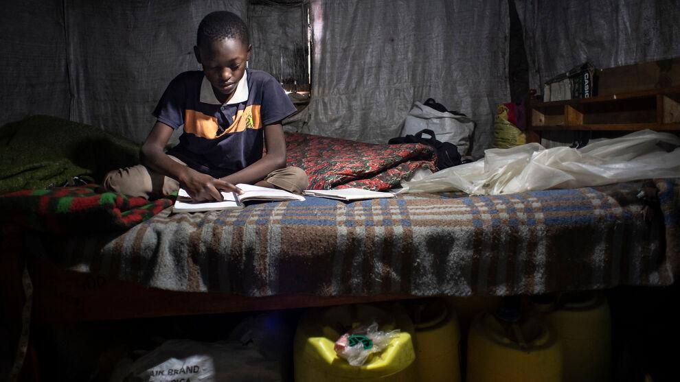 Kenia: Rafael, 11 vuotta, lukee kuudennen luokan oppikirjaa. Hän ei voi osallistua etäopetukseen, koska perheellä ei ole varaa kännykkään. © UNICEF/UNI362245/Everett