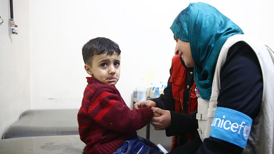 UNICEFin ravintoasiantuntija Rajia Sherhan tarkistaa lapsen tilannetta terveyskeskuksessa Doumassa, itäisessä Ghoutassa. Kuva: © UNICEF/UN0185389/Khabieh