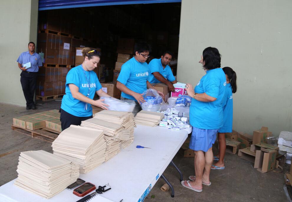 UNICEFin henkilökunta ja vapaaehtoiset pakkaavat vesi-, sanitaatio- ja hygieniatarvikepaketteja sekä koulutarvikkeita UNICEFin varastolla Fidzin pääkaupungissa Suvassa. © UNICEF/UN010931/Hing