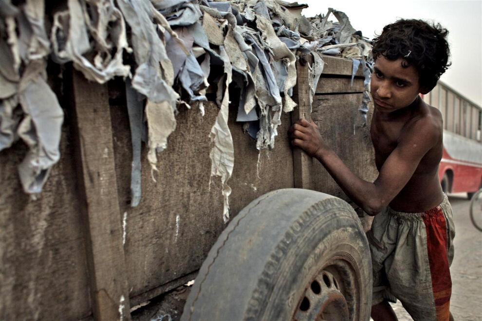 12-vuotias lapsityöläinen Nawab Hali työntää nahanriekaleilla täytettyä kärryä Dhakan alueella Bangladeshissa. Nawab valmistaa nahasta rakennusliimaa, mikä altistaa hänet monille vaarallisille kemikaaleille. © UNICEF/UNI118476/Noorani