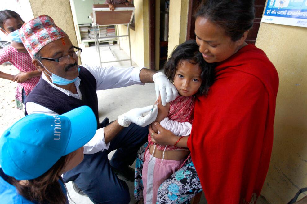 Neljävuotias Neisha Shakya saa tuhkarokko- ja vihurirokkorokotuksen Bungamatin terveysasemalla Kathmandun laaksossa. Neishan äiti Indu Maharjan toi tyttärensä terveysasemalle kuultuaan rokotuksista. Perhe asuu tilapäisessä telttakylässä.