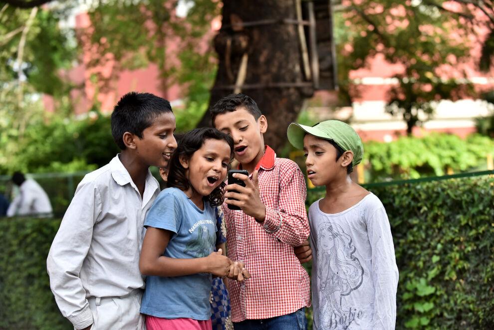 Intialaislapset käyttävät matkapuhelinta koulun pihalla Delhissä. Kuva: © UNICEF/Intia/Sharm