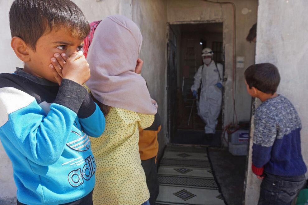 Lapset seuraavat, kuinka entistä koulurakennusta desinfioidaan maaliskuun 26. päivä Binnishin kaupungissa Syyriassa. Rakennus toimii nyt maansisäisten pakolaisten hätämajoituksena. © UNICEF/UNI316131/Haj Kadour/AFP
