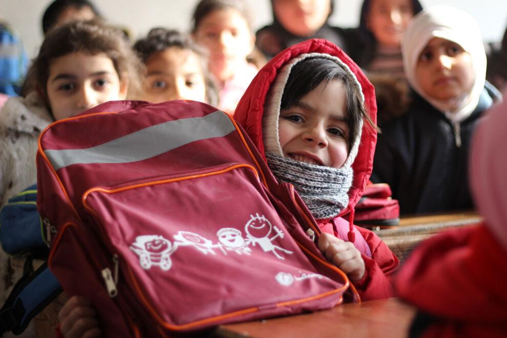 7-vuotias itäaleppolainen Fatima esittelee uutta koulureppuaan, jonka hän sai UNICEFilta. © UNICEF/UN051524/Al-Issa