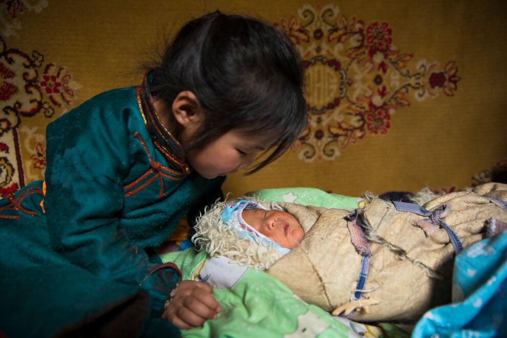 UNICEF työskentelee eri puolilla maailmaa, jotta vastasyntyneillä olisi paremmat mahdollisuudet selvitä hengissä. Mongoliassa tapasimme Batyargal Margadman (4 vuotta) katselemassa uutta pikkusiskoaan Sugarmaa Batjargalia (8 päivää). UNICEF on kouluttanut alueen äitejä lastenhoidossa vuodesta 2014 lähtien. © UNICEF/UN0198622/Njiokiktjien VII Photo