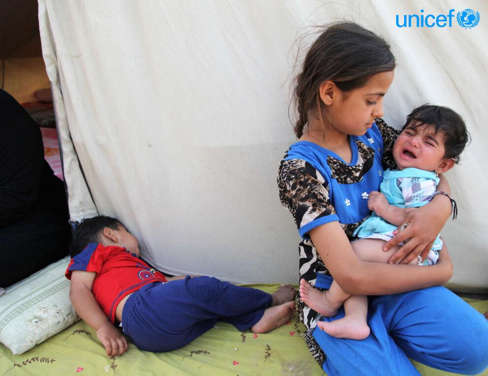 Tyttö lohduttaa itkevää pikkulasta pakolaisleirillä Karkhissa Irakissa. © UNICEF/UNI183543/Khuzaie