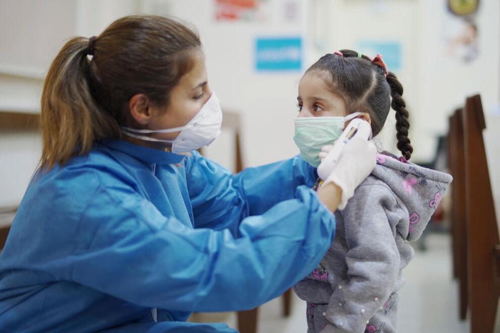 Sairaanhoitaja mittaa, onko lapsella kuumetta UNICEFin tukemassa terveyskeskuksessa Beirutissa, Libanonissa. UNICEFin kautta voit auttaa pysäyttämään koronan kaikkialla. © UNICEF/UNI317998/Choufany