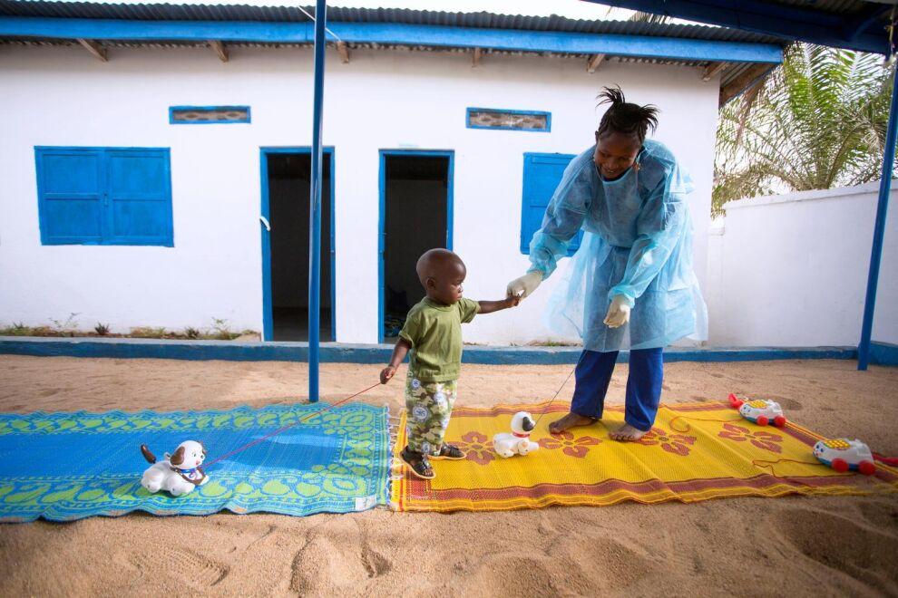 Puolitoistavuotias Tamba menetti äitinsä ebolalle ja joutui 21 päiväksi karanteeniin tartuntavaaran vuoksi. Ebolasta selvinnyt Rose Komano leikitti Tambaa UNICEFin tukemassa keskuksessa Guineassa tammikuussa 2015.
