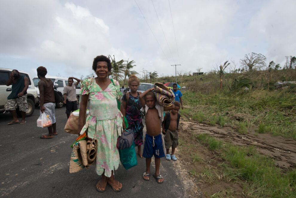 Myrskytuhoja pakeneva perhe kantoi tavaroitaan Vanuatun pääkaupungin Port Vilan laitamilla sunnuntaina 15. maaliskuuta.