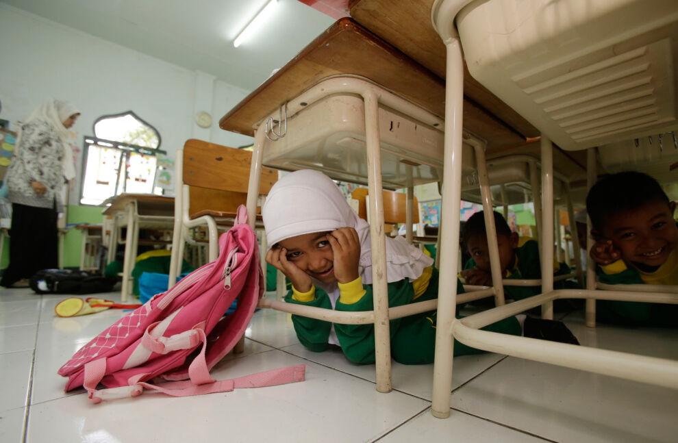 Koululaisia harjoittelemassa maanjäristystilanteessa toimimista Indonesiassa. © UNICEF/PFPG2014-1355/Unknown
