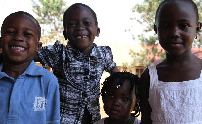Lapset pysähtyivät poseeraamaan terveystarkastuksen jälkeen Magindyessa, Ugandassa.