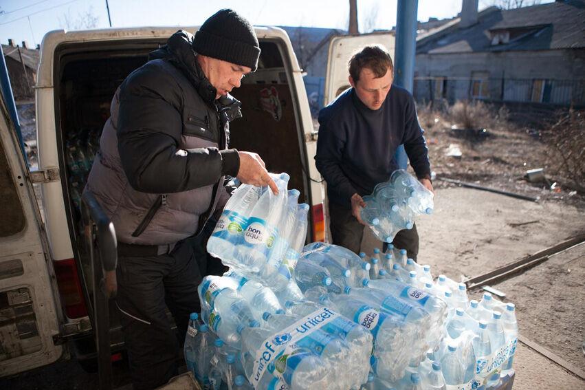 Vapaaehtoiset purkavat vesipullokuormaa Debaltsevon kaupungissa Donetskin alueella helmikuussa 2015. © UNICEF/NYHQ2015-0279/Filippov