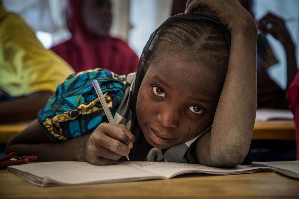 UNICEF tarjoaa kriisialueen lapsille vaihtoehtoisia mahdollisuuksia oppimiseen. Kuvan tyttö saa oppia väliaikaisessa opetustilassa pakolaisleirillä Diffan alueella Nigerissä. © UNICEF/UN055323/Tremeau