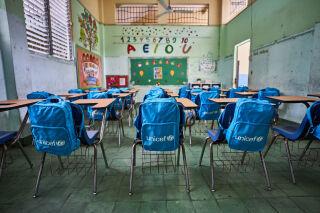Tyhjä luokkahuone, jossa tuolien selkänojilla UNICEF-reppuja