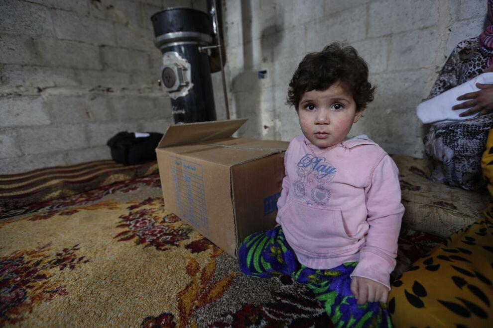 Syyrialaistyttö istuu UNICEFin talvivaatepaketin vieressä. Lähestyvä talvi uhkaa erityisesti lapsia. Kuva: © UNICEF/UN02854/Sanadiki