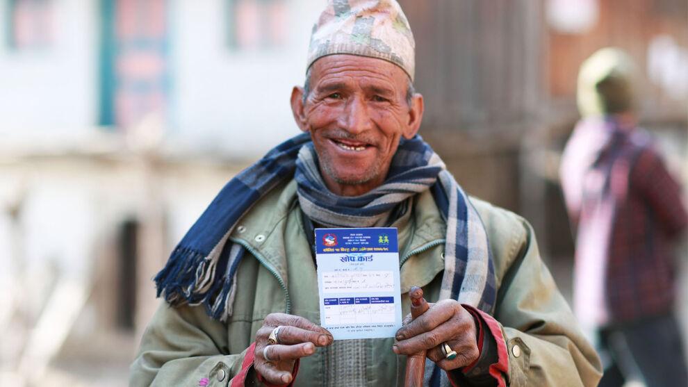 Riskiryhmään kuuluva Karnajit Rawat, 68, asuu Nepalin maaseudulla Kandasundarissa. Hän on juuri saanut ensimmäisen koronarokotuksen ja pitelee käsissään rokotustodistusta.