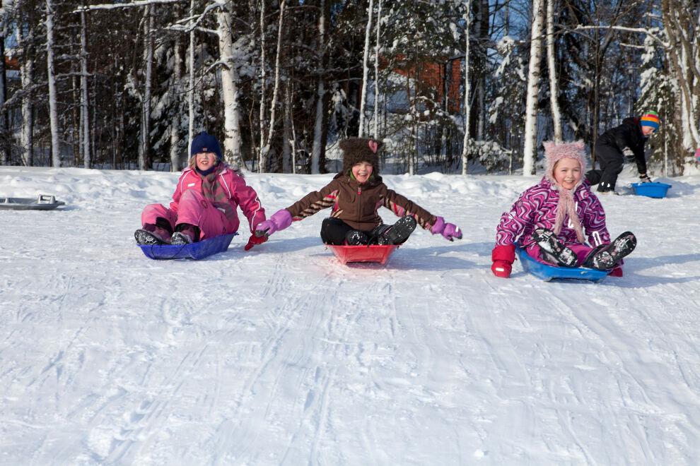 Lapset laskevat pulkkamäkeä talvella.