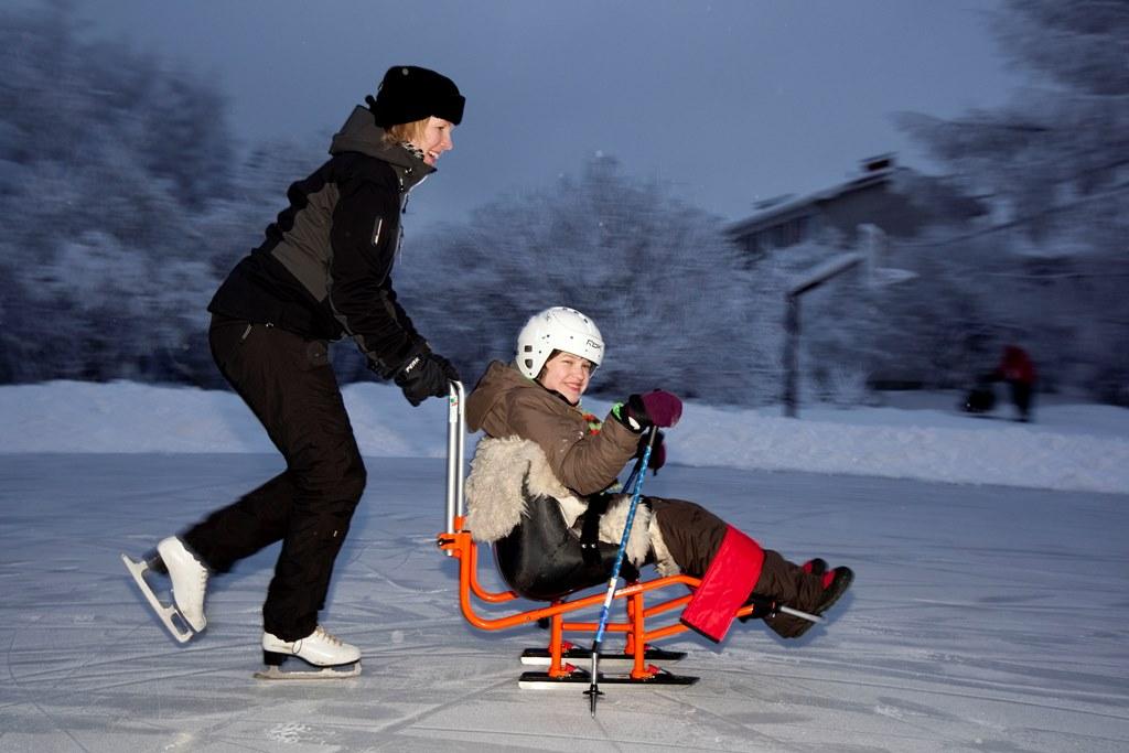Lapsi ja ohjaaja talvileikeissä.