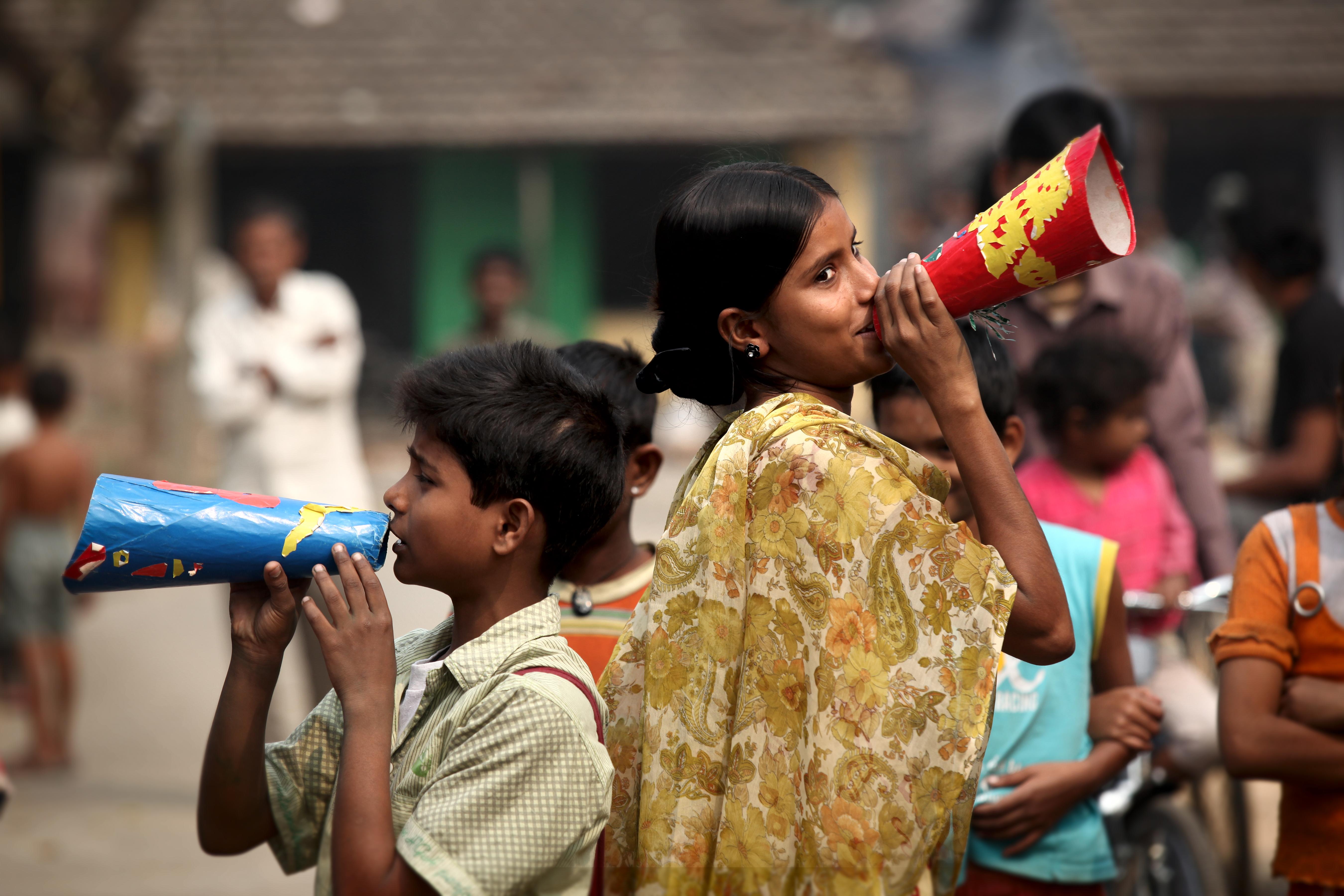 Kuva Intiasta: lapset värikkäiden megafonien kanssa