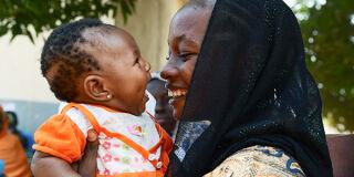 Äiti ja lapsi halaavat ja hymyilevät.